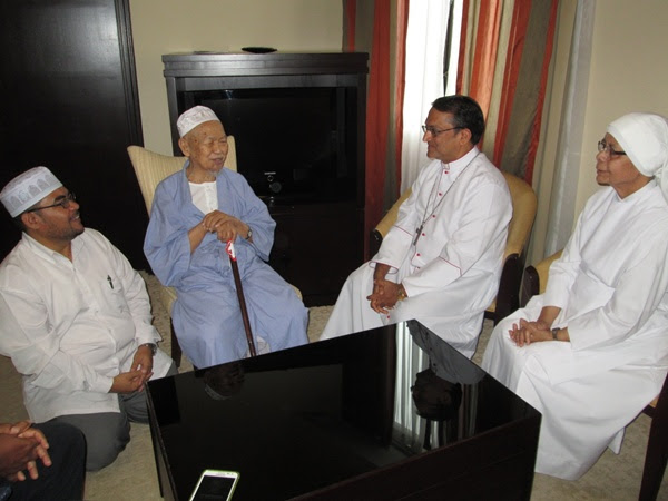 Tok Guru Nik Aziz engages in dialogue with Bishop Sebastian Francis. They are flanked by Mujahid Yusof Rawa (left) and Sister Marie Jeanne (right)