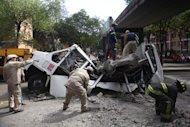Firefighters work to remove a cement beam that fell from a bridge onto a public bus after an earthquake was felt in Mexico City Tuesday March 20, 2012. A strong 7.4-magnitude earthquake hit central and southern Mexico on Tuesday, collapsing at least 60 homes near the epicenter and a pedestrian bridge in the capital where people fled shaking office buildings in fear. There were no passengers in the mini-bus and the driver suffered minor injuries, according to firefighters. (AP Photo/Alexandre Meneghini)