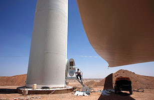 A worker prepares for the installation of giant rotor blades atop a wind-turbine tower in China's Gansu province