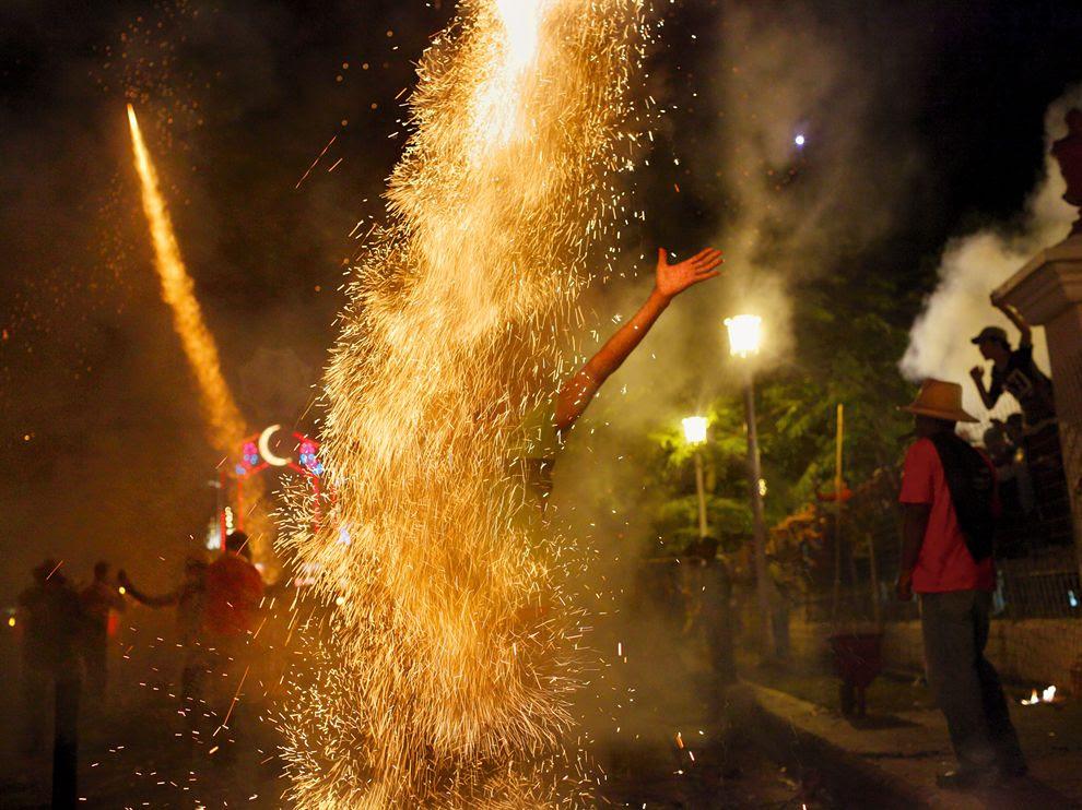 Πυροτεχνήματα περιβάλλουν έναν συμμετέχοντα στο φεστιβάλ Parrandas στην πόλη Remedios της Κούβας.