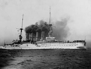 A large warship steams at full speed; black smoke billows from its four funnels