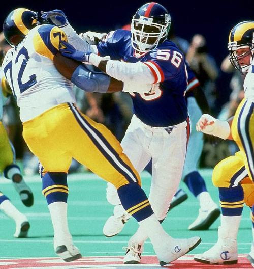 siphotos:<br /><br />Giants linebacker Lawrence Taylor pushes Rams tackle Robert Jenkins aside on Sept. 8, 1991 at Giants Stadium in East Rutherford, NJ.  10-time Pro Bowler and 8-time First-Team All-Pro Hall of Famer L.T. turns 55 today. (John Iacono/SI)<br />