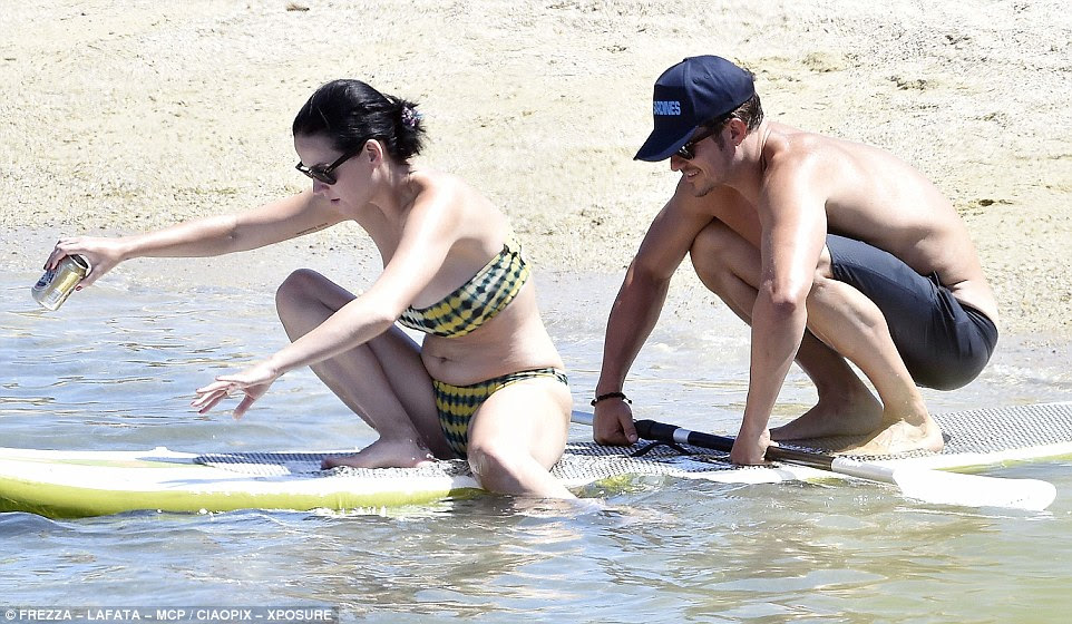 I got you babe: Orlando steadied the board as Katy climbed on with her drink in hand