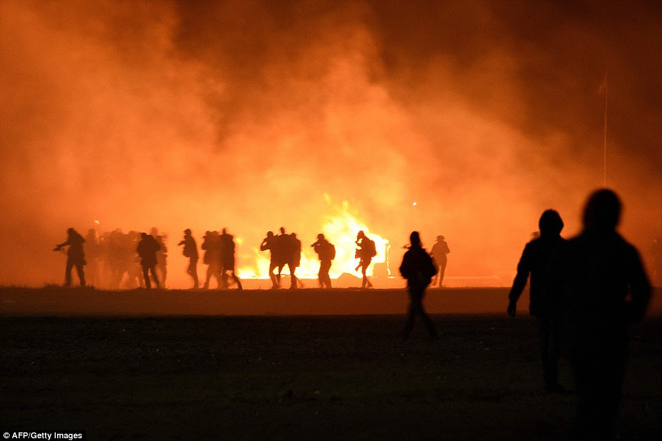 Smoke billows after migrants started fires, leaving an orange mist at the camp were tensions with ahuthorities run high