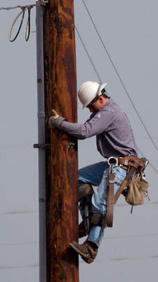 Cropped version:A worker climbing down an elec...