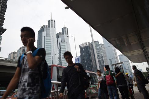 People walk past buildings in the central business district in Beijing on Sept. 9, 2015.