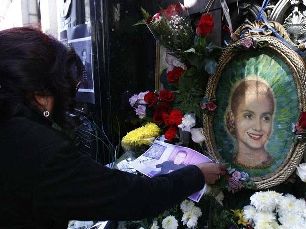 Uma mulher coloca uma foto de um parente desaparecido no túmulo do ex-primeira-dama Eva Perón, para comemorar o 60 º aniversário de sua morte no cemitério da Recoleta, em Buenos Aires. (Foto: Marcos Brindicci/Reuters)
