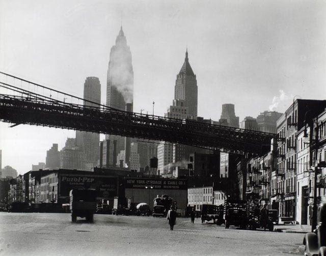 Waterfront, South Street, Manhattan. Brooklyn Bridge span as it reaches land above South Street near James, tall buildings rise beyond.