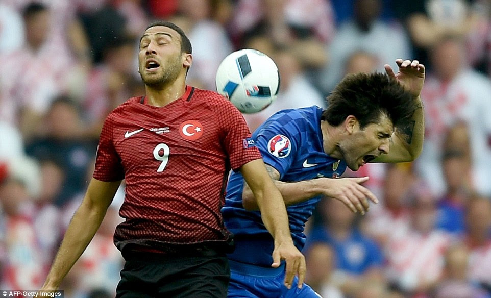 Vedran Corluka of Croatia went down holding his head after getting caught by Turkey's Cenk Tosun in the first half in Paris