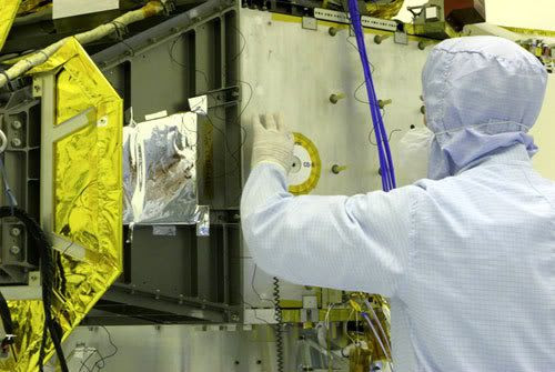 An engineer installs a compact disc bearing the names of 434,738 people onto the side of the New Horizons spacecraft...prior to launch in January of 2006.