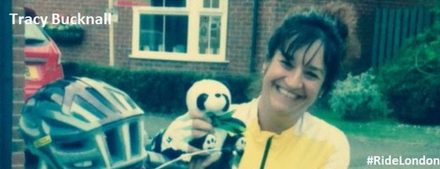 Tracy Bucknall holding a cuddly toy panda in her garden, just in view here cycle helmet rests on her handle bars of her bike