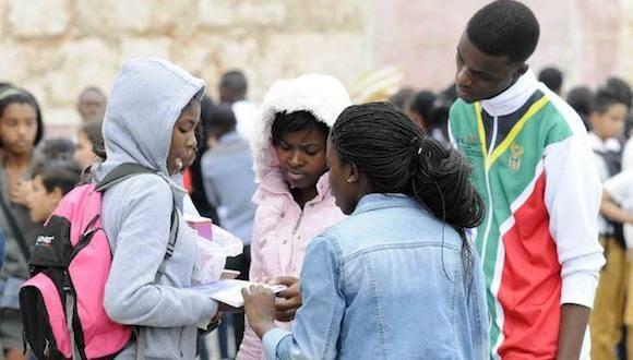 Estudiantes extranjeros observando libros adquiridos en la Fortaleza San Carlos de La Cabaña, sede principal de la XXIV Feria Internacional del Libro, durante la llegada de un frente frio a La Habana, Cuba, el 18 de febrero de 2015.  AIN FOTO/Roberto  MOREJÓN RODRÍGUEZ/