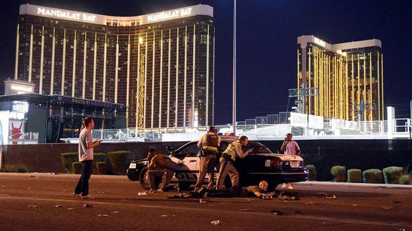 Police officers and regular citizens take cover behind a cop car after a gunman opened fire on a country music concert in Las Vegas...on October 1, 2017.