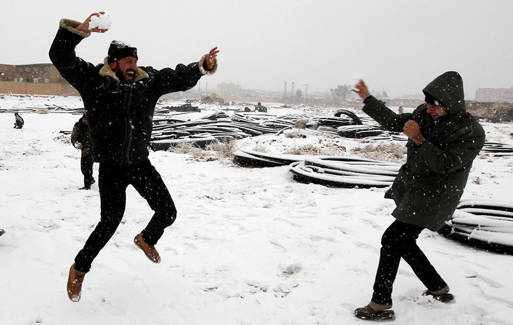 Free Syrian Army fighters play with snow in the eastern city of Raqqa. (REUTERS/Nour Fourat)