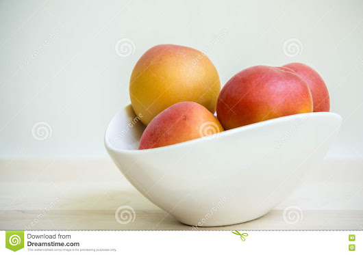 Apricots in white bowl.