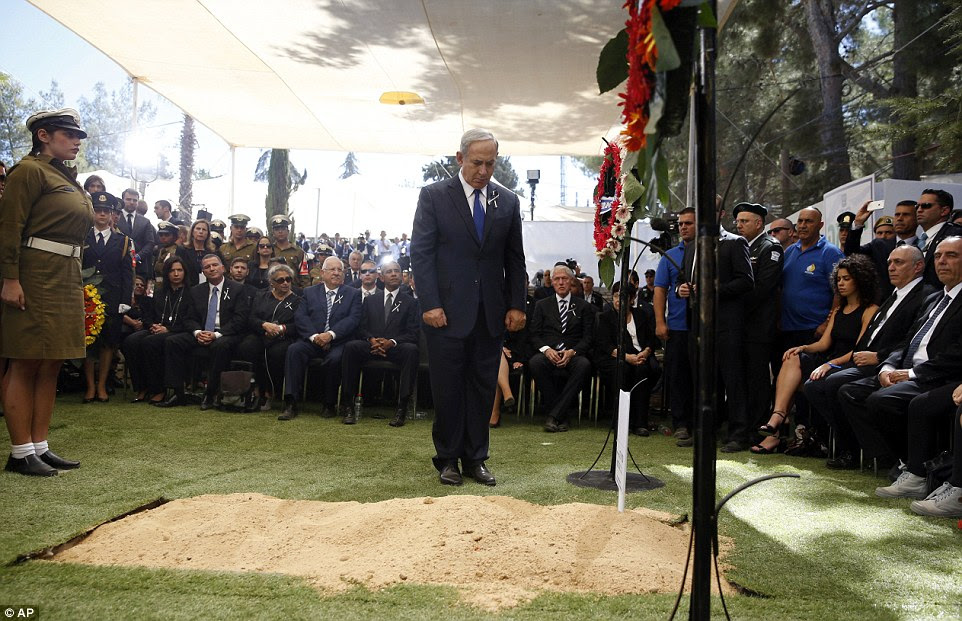 O primeiro-ministro israelense, Benjamin Netanyahu inclina a cabeça e observa um minuto de silêncio após depositar uma coroa perto do túmulo de Shimon Peres