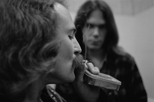 "July, 12th 1970--  David Crosby smokes ""something"" in the backstage bathroom while Neil Young looks on.  -- Image by © Henry Diltz"