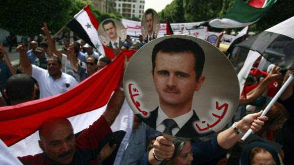 """Pro-Syrian demonstrators display placards with the image of the Syrian President Bashar Assad during a demonstration against possible military action against Syria in Tunis, Tunisia, on Friday, Aug. 30, 2013. The writing on the placard reads, """"We are with you."""""""