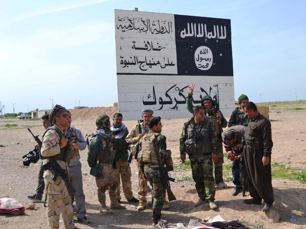 Iraqi Kurdish Peshmerga fighters stand next to an Islamic State group sign at the entrance to the northern Iraqi town of Hawija, south of Kirkuk on March 9, 2015