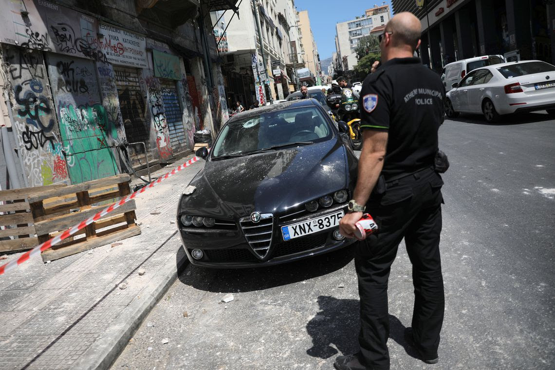 A police officer stands on a street next to a damaged car following an earthquake in Athens, Greece, July 19, 2019.  REUTERS/Alkis Konstantinidis
