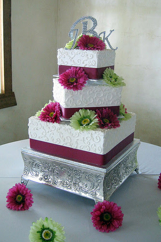 square wedding cakes with flowers. The flowers will be stargazer