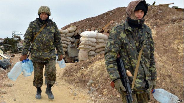 Soldados cargando botellas vacías de agua