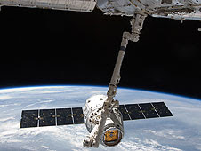 SpaceX Dragon as ISS arm reaches out to grab.