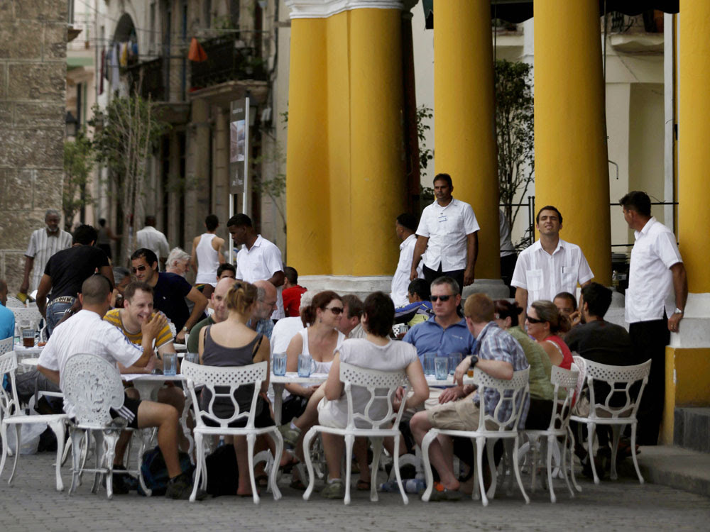 Tourists sit  outside a bar in Old Havana