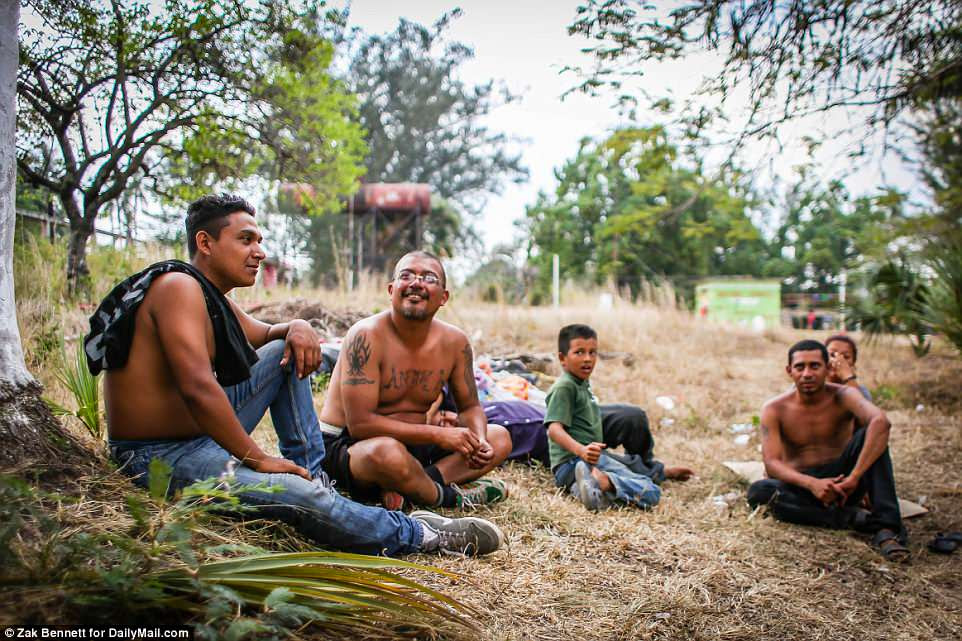 Marvin Geovanni Alvarez, 39, of El Salvador, and others relax in a field inMatÌas Romero, Oaxaca, Mexico. Alverez was targeted by MS-13 gangsters after returning to El Salvador, stabbed three times - once in the head - and warned he would be murdered if he didn't join up