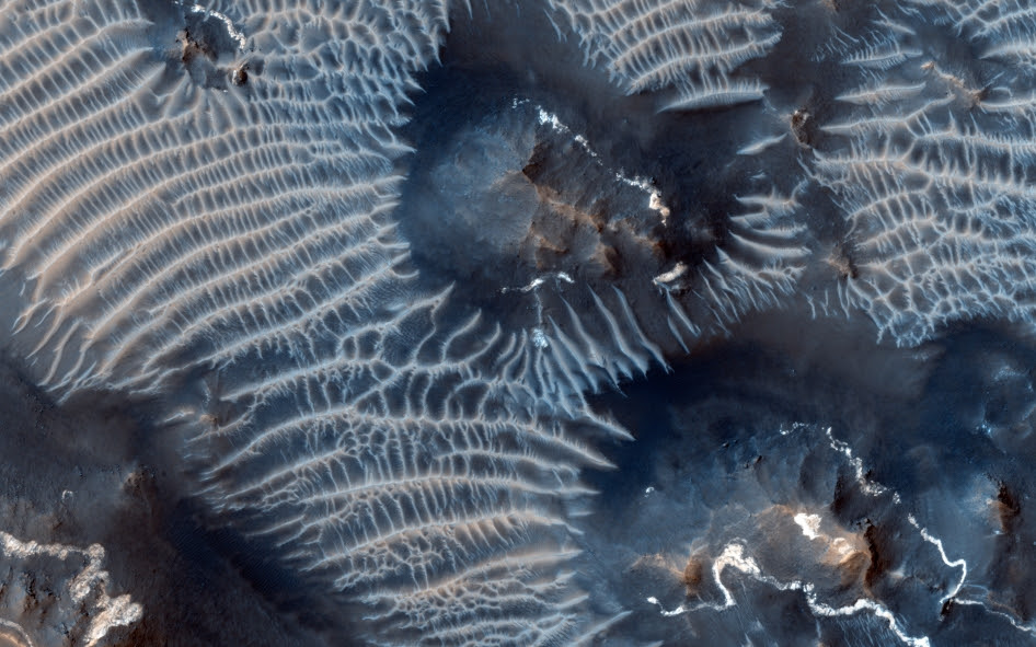 This colorful scene is situated in the Noctis Labyrinthus region of Mars, perched high on the Tharsis rise in the upper reaches of the Valles Marineris canyon system.