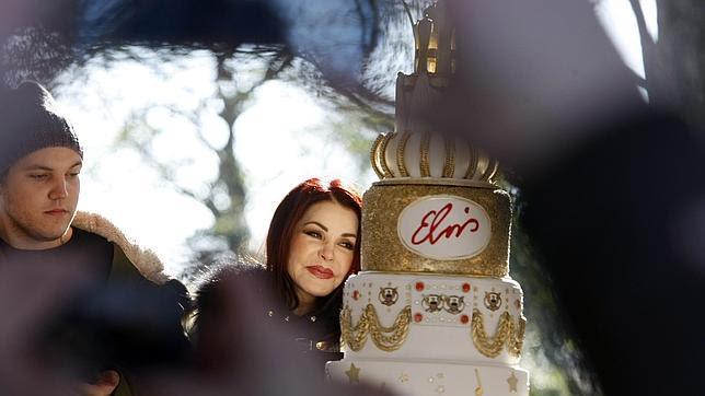 Priscilla Ann Presley ante el pastel de ocho pisos que más tarde cortaría junto a la hija de ambos