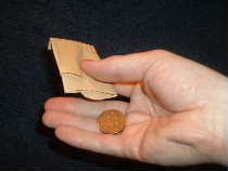 Turn pouch upside down and allow the coin to fall into the palm of your hand.
