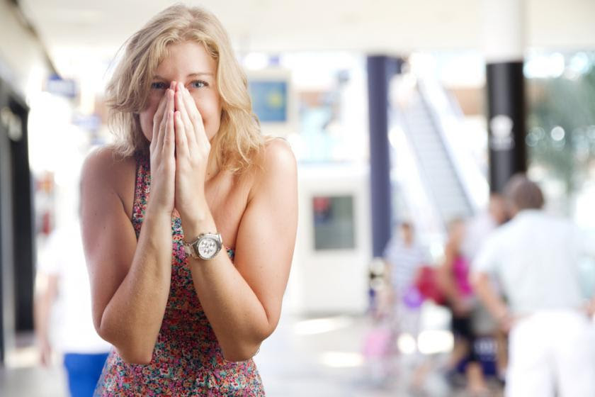 Young woman covering her mouth in a shopping center
