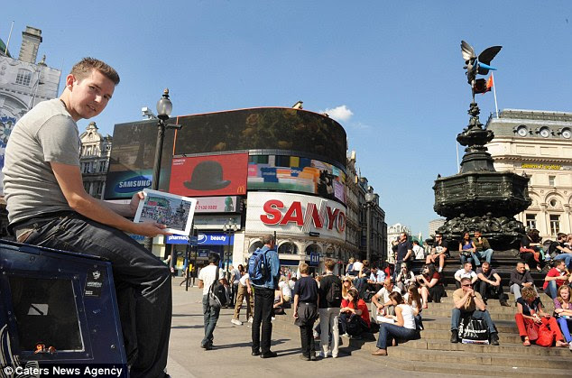 Iconic: Kyle sits in Piccadilly Circus to recreate a spot of London that is rarely free of people