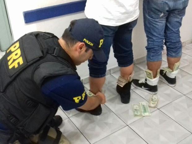 Policial recolhe dólares sem origem comprovada em meia de homem (Foto: Polícia Rodoviária Federal / Divulgação)