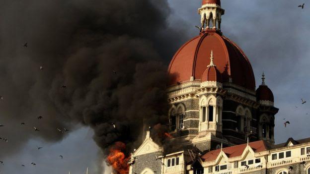 Flames and smoke gush out of the historic historic Taj Mahal Hotel in Mumbai on November 27, 2008