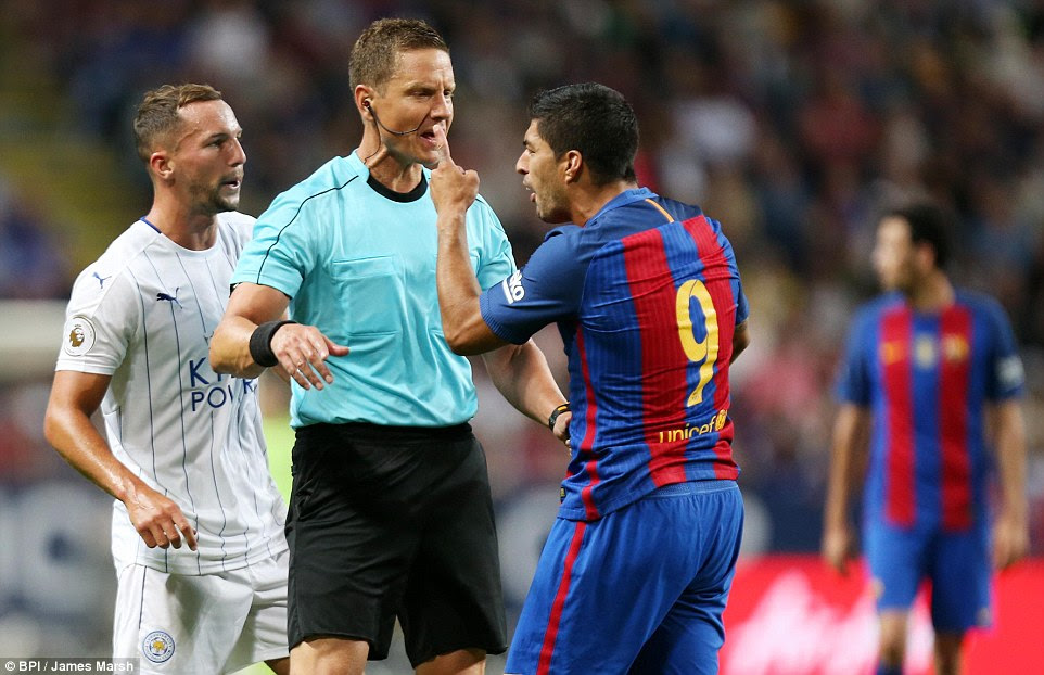 Luis Suarez remonstrates with the referee while Danny Drinkwater watches on during the clash on Wednesday night