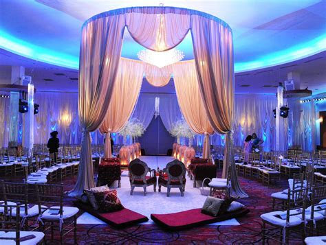Elegant Indian wedding ceremony with a gold mandap up lit