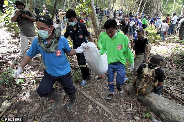 Recovered: Rescuers spent a second day carrying away the bodies (pictured) of dead migrants in Songkhla province