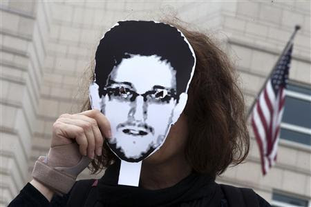 A woman holds a portrait of former U.S. spy agency contractor Edward Snowden in front of her face as she stands in front of the U.S. embassy during a protest in Berlin, in this file photo from July 4, 2013. REUTERS/Thomas Peter/Files