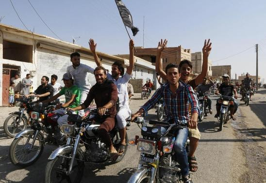 Residents of Tabqa city tour the streets on motorcycles, carrying flags in celebration after Tabqa air base fell to Islamic State militants, in nearby Raqqa city August 24, 2014. REUTERS-Stringer