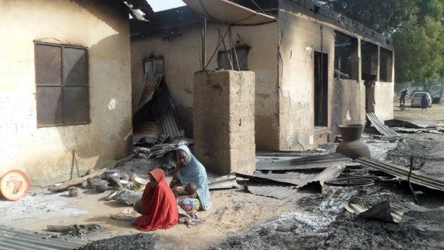 Nigerianas em frente à residência incendiada