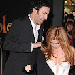 Ever the gentleman! Isla Fisher steals the spotlight from husband Sacha Baron Cohen in plunging white gown... but he still offers his coat