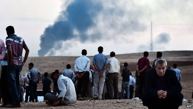 Kurdish people stand on a hill at the Turkish-Syrian border in the south-eastern village of Mursitpinar, Sanliurfa province, on 9 October 2014.