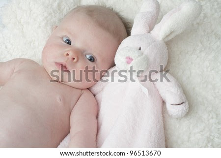 Adorable Baby Lying On Soft Furry Blanket Cuddling With Pink Toy