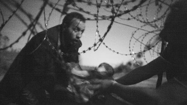Esperanza de una nueva vida. El trabajo inédito de Warren Richardson fue destacado como foto del año; la imagen se obtuvo ?a las 3 de la mañana del 28 de agosto en la frontera entre Hungría y Serbia, sin más luz que la de la luna