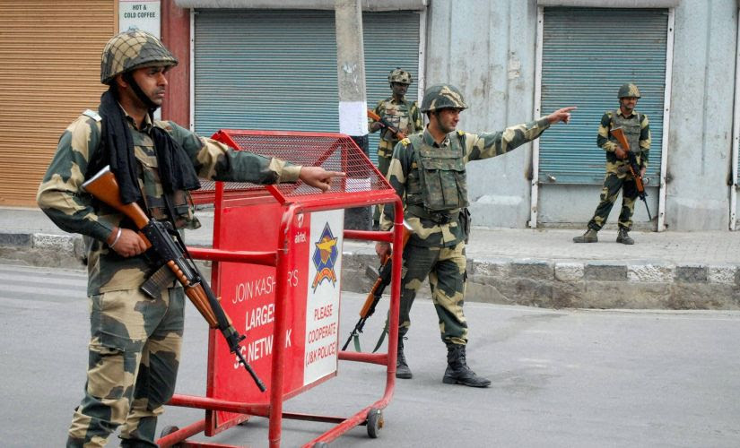 BSF Jawans guard the streets during curfew in Srinagar on Monday. PTI