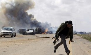 Rebel fighter runs for cover in front of vehicles