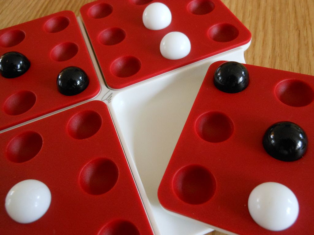 A game of Pentago in progress, with board rotating to line up black balls.