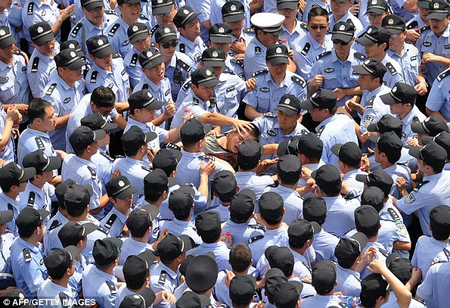 Outnumbered: Police swarm around a protestor outside the local government offices in the coastal city of Qidong following demonstrations